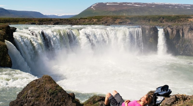 Woman Hiker resting At Godafoss Waterfall Iceland -  istock.JPG